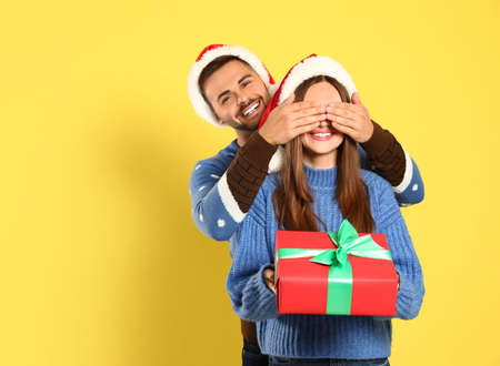 Couple wearing Christmas sweaters and Santa hats on yellow background