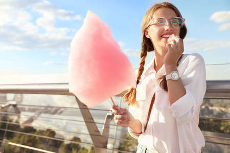 Young woman with cotton candy outdoors on sunny day