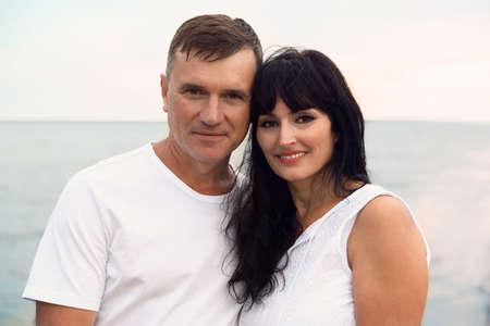 Feliz pareja madura pasar tiempo juntos en la playa del mar