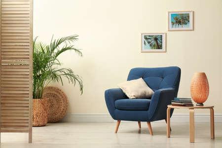 Interni eleganti con mobili confortevoli e piante vicino al muro beige Archivio Fotografico
