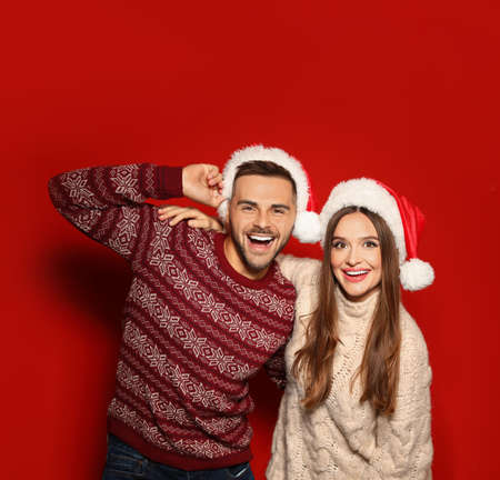 Couple wearing Christmas sweaters and Santa hats on red background