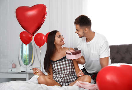 Young man presenting gift to his girlfriend in bedroom decorated with air balloons. Celebration of Saint Valentines Day