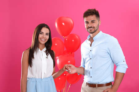 Young couple and air balloons on pink background. Celebration of Saint Valentines Day