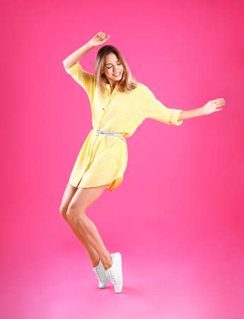 Beautiful young woman in yellow dress dancing on pink background