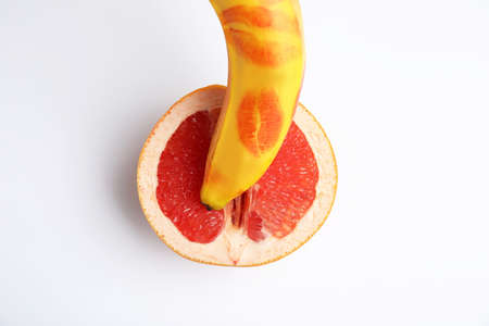 Fresh grapefruit and banana with red lipstick marks on white background, top view. Sex concept