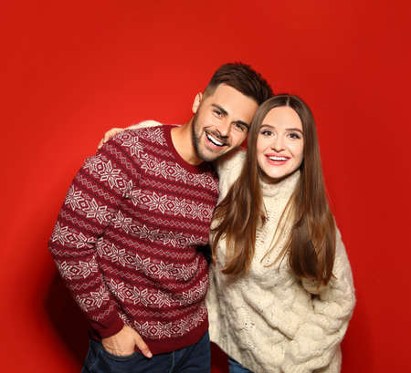 Couple wearing Christmas sweaters on red background