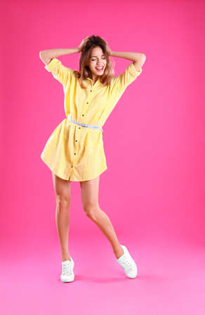 Beautiful young woman in yellow dress dancing on pink background Stock Photo - 128832619