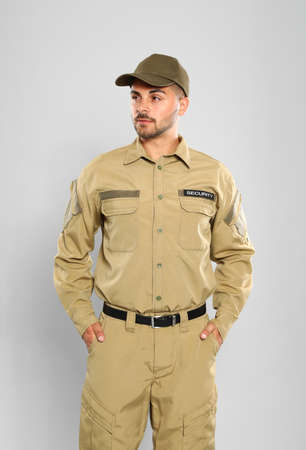 Male security guard in uniform on grey background
