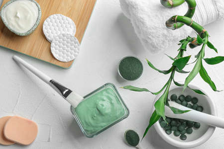 Flat lay composition with spirulina facial mask and ingredients on white table 写真素材