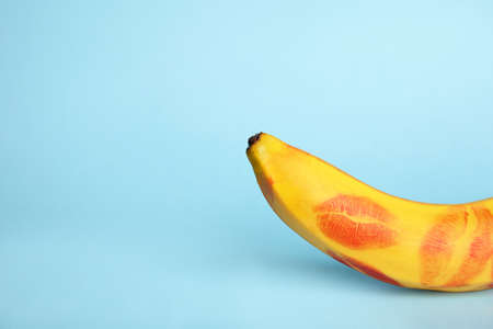 Fresh banana with red lipstick marks on blue background, space for text. Oral sex concept