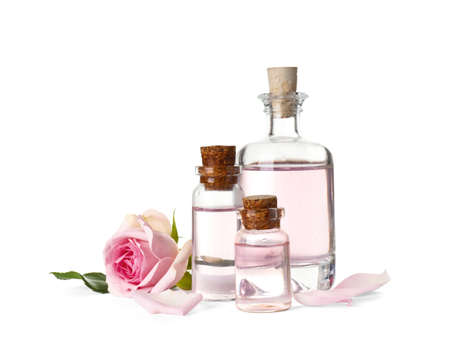 Bottles of essential oil and rose on white background