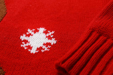 Warm red Christmas sweater with snowflake as background, closeup view Stock fotó