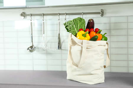 Textile shopping bag full of vegetables on countertop in kitchen. Space for text