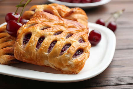Fresh delicious puff pastry with sweet cherries served on wooden table, closeup