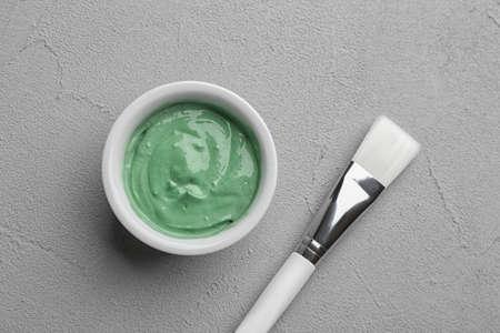 Spirulina facial mask and brush on light grey table, flat lay