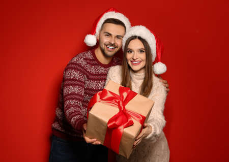 Couple in Christmas sweaters and Santa hats with gift box on red background Stockfoto