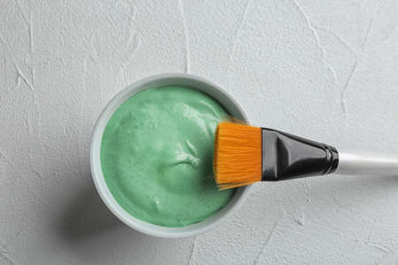 Spirulina facial mask and brush on white table, flat lay