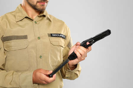 Male security guard in uniform with gun on grey background, closeup