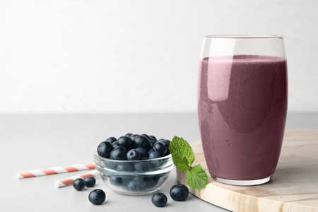 Fresh acai drink with berries on grey table against light background. Space for text Stock fotó