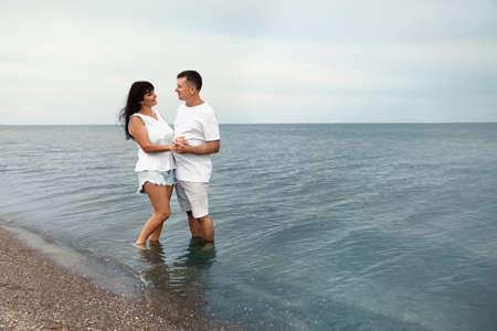 Feliz pareja madura pasar tiempo juntos en la playa del mar. Espacio para texto