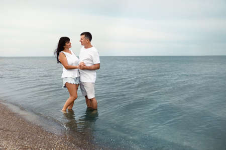 Happy mature couple spending time together on sea beach. Space for text