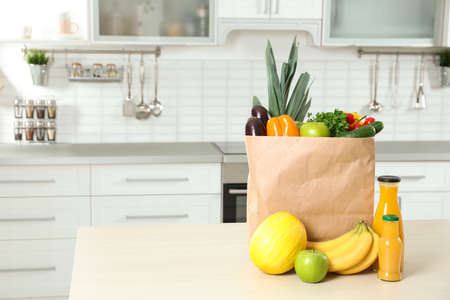 Paper shopping bag full of vegetables with fruits and juice on table in kitchen. Space for text