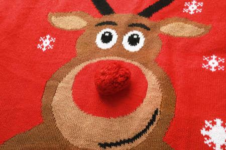 Maglione rosso caldo di Natale con i cervi come fondo, vista del primo piano