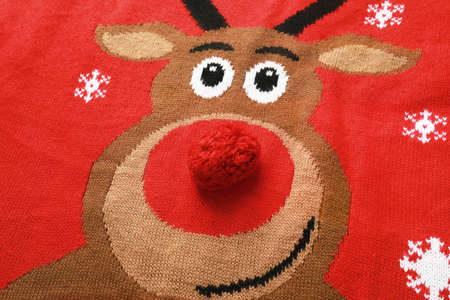 Warm red Christmas sweater with deer as background, closeup view