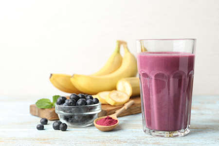 Fresh acai drink with berries and bananas on wooden table against light background