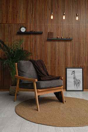 Stylish room interior with comfortable armchair and plant near wooden wall