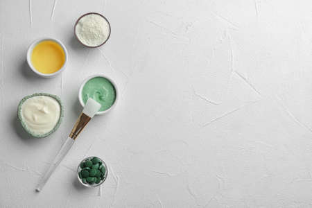 Flat lay composition with spirulina facial mask and ingredients on white table. Space for text 写真素材