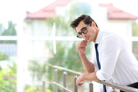 Bel giovane in abiti eleganti con gli occhiali al chiuso. Spazio per il testo Archivio Fotografico