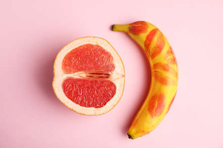 Fresh grapefruit and banana with red lipstick marks on pink background. Sex concept
