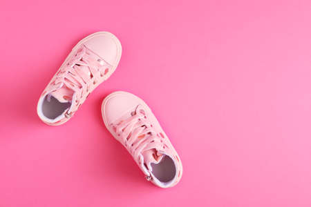 Pair of stylish child shoes on pink background, flat lay. Space for text 免版税图像