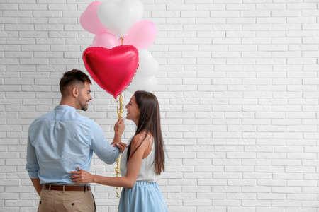Jeune couple avec des ballons à air près du mur de briques blanches. Célébration de la Saint-Valentin
