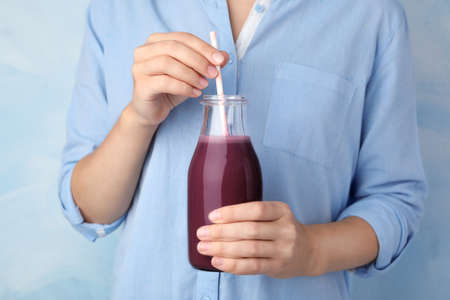 Woman with bottle of fresh acai drink and straw, closeup