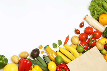 Shopping paper bag with different groceries on white background, top view