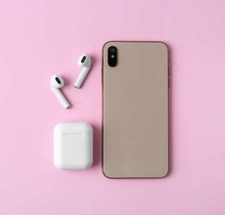 Wireless earphones, mobile phone and charging case on pink background, flat lay