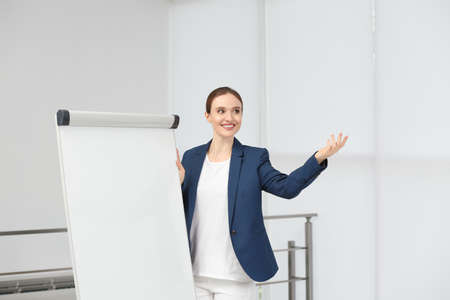 Professional business trainer near flip chart board indoors. Space for text