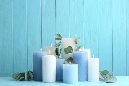 Set brennender Kerzen mit Eukalyptus auf dem Tisch vor hellblauem Holzhintergrund