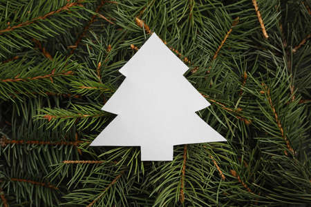 Christmas tree cut out of paper on branches, top view