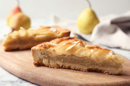 Board with pieces of delicious sweet pear tart on table, closeup
