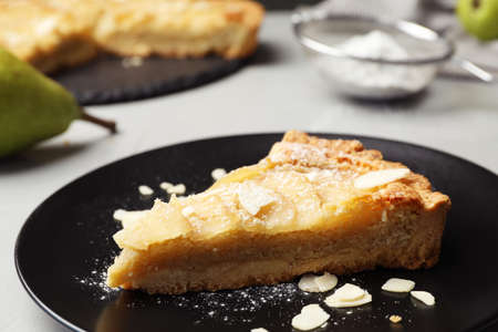 Piece of delicious sweet pear tart on table, closeup