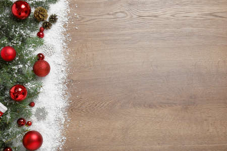 Christmas decoration with snow on wooden background, flat lay. Space for text