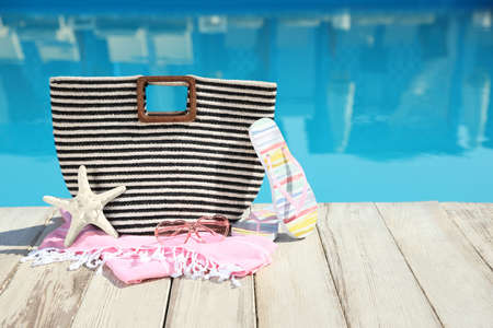 Beach accessories on wooden deck near outdoor swimming pool, space for text