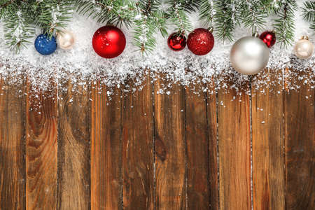 Christmas decoration with white snow on wooden background, flat lay. Space for text