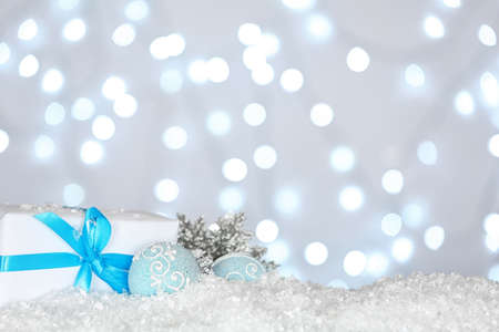 Christmas decoration and gift box on snow against blurred background, space for text