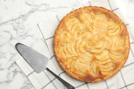 Delicious sweet pear tart with spatula on white marble table, flat lay Imagens