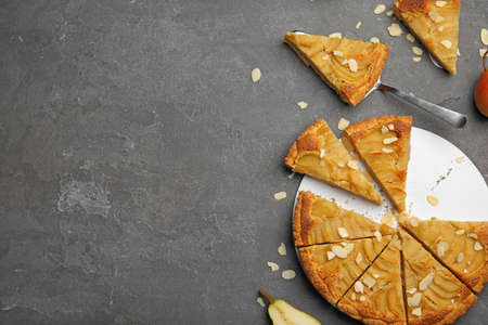 Cut delicious sweet pear tart and spatula on grey table, flat lay. Space for text Imagens