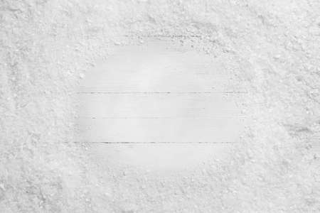 Frame of snow on white wooden background, top view with space for text. Christmas season